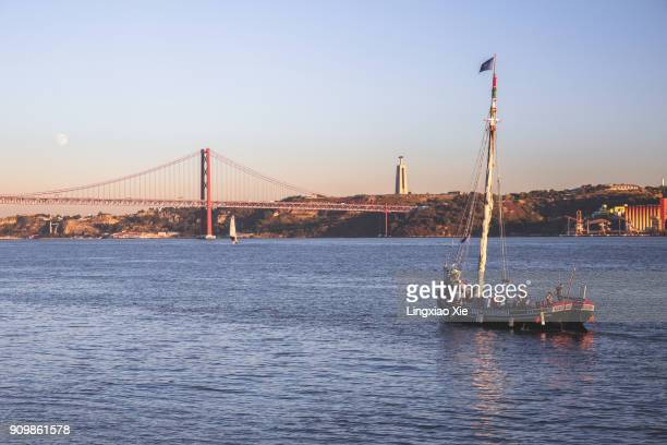 Sailing boat on Tagus River with the famous 25 de Abril Bridge, Lisbon, Portugal