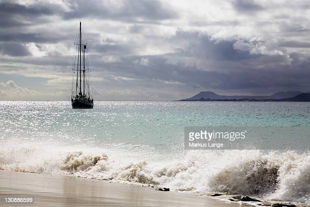 sailing boat on the playa de mujeres beach near playa blanca, fuerteventura in the back, lanzarote, canary islands, spain, europe - mujeres fotos stockfoto's en -beelden