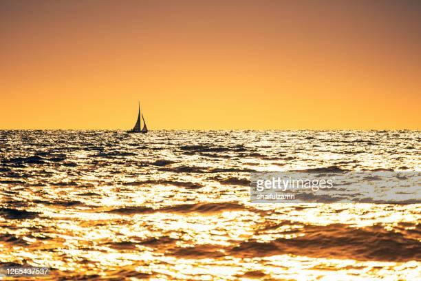 sailing boat over sunrise - shaifulzamri stock pictures, royalty-free photos & images