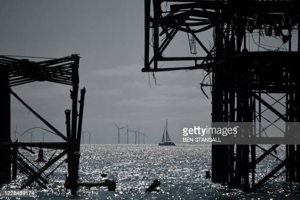 Sailing boat passes between the derelict West Pier and the off-shore wind farm in Brighton, on the south coast of England on September 13 the day...