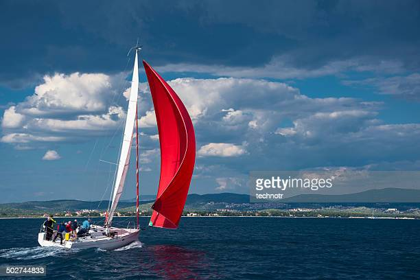 Sailing boat using red genacker against cloudy sky