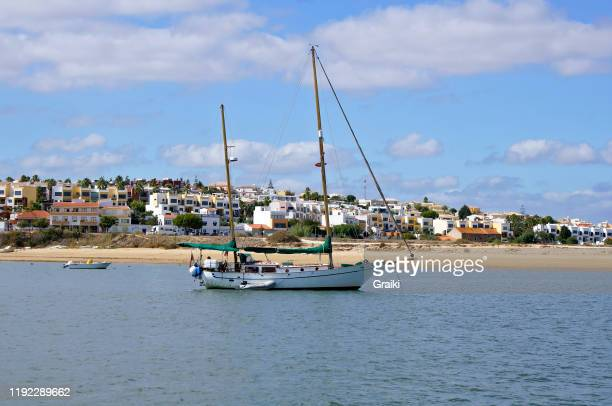 sailing boat with the beach and fishing district in the background. - ポルティマン ストックフォトと画像
