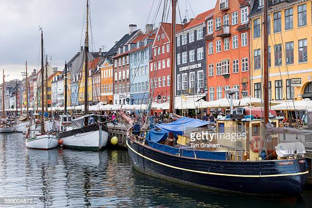 Sailing boats at famous Nyhavn 17th Century waterfront canal and entertainment district on June 21 2015 in Copenhagen Denmark