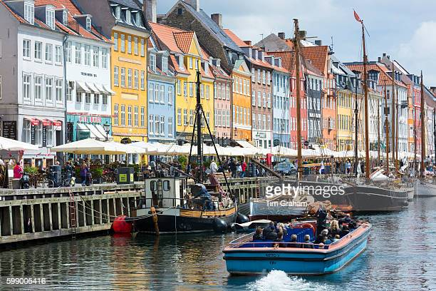 Sailing boats at famous Nyhavn 17th Century waterfront canal and entertainment district on June 22 2015 in Copenhagen Denmark