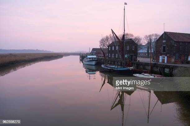sailing boats moored at harbour wall, reflected on the surface of a calm canal at twilight. - east anglia stock pictures, royalty-free photos & images