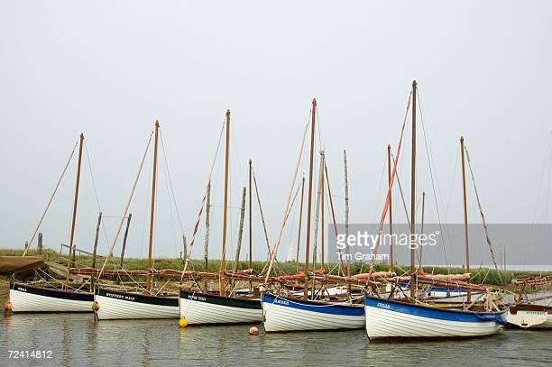 Sailing boats moored at Morston Quay near Blakeney North Norfolk United Kingdom