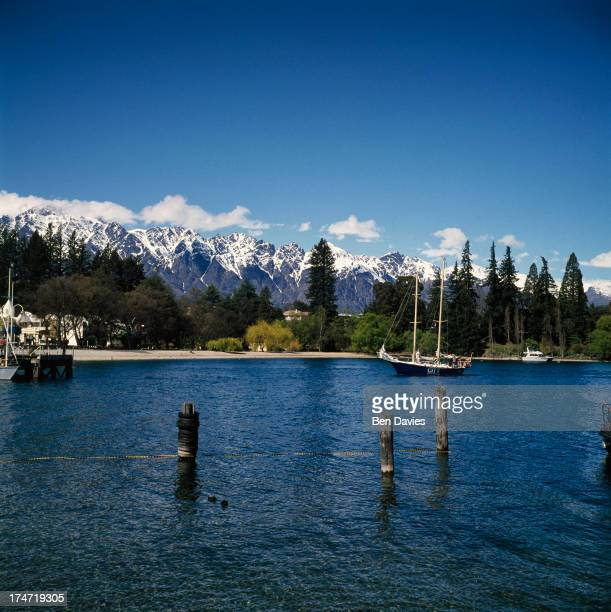 Sailing boats on beautiful Lake Wakatipu framed by snowy mountain peaks and fjords at Queenstown on New Zealand's South Island A major tourist...