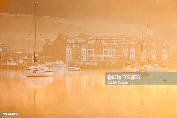 Sailing boats on Lake Windermere at Waterhead, Ambleside in the Lake District, Cumbria, UK, at dawn.