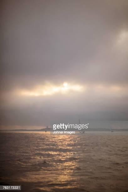 Sailing boats on sea at sunset