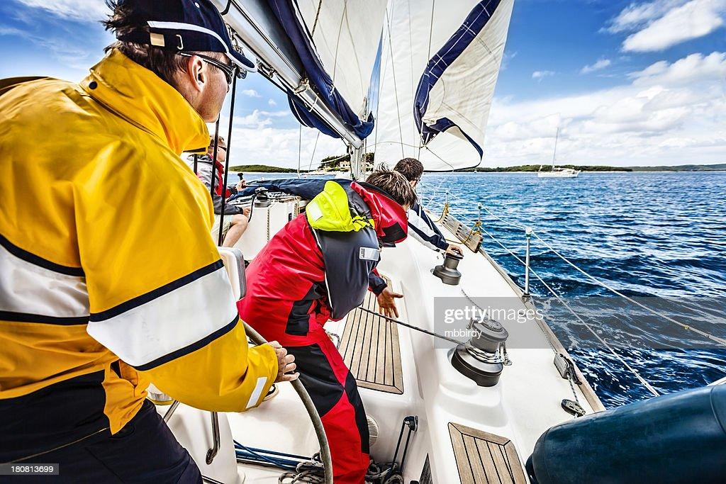 Sailing crew beating to windward on sailboat : Stock Photo