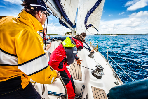 Sailing crew beating to windward on sailboat 180813699