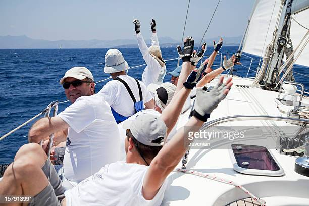 Sailing crew on deck with most hands raised