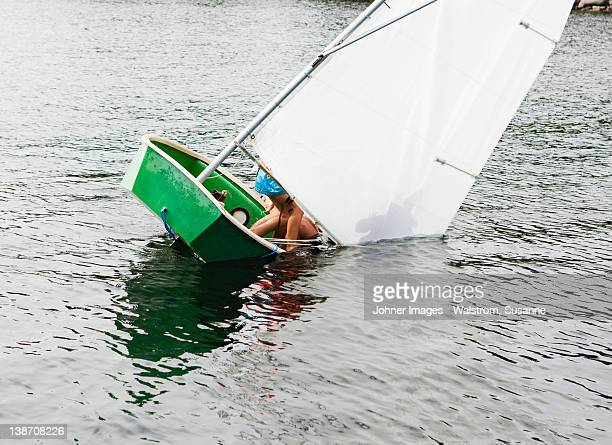 Sailing dinghy falling into water