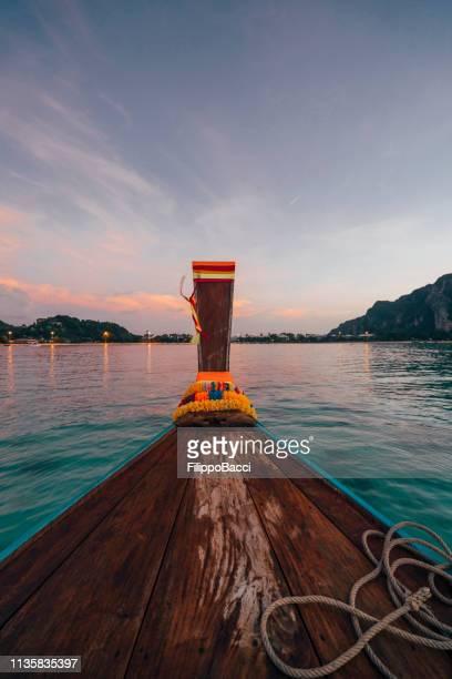 segeln auf einem langen schwanzboot bei sonnenuntergang auf phi phi island, thailand - asiatisches langboot stock-fotos und bilder