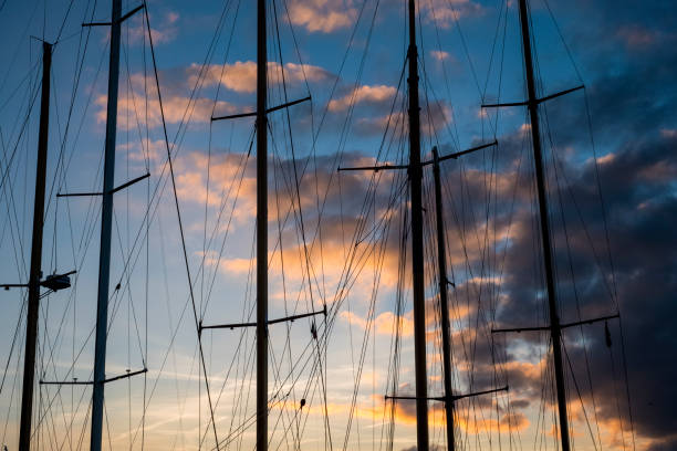 Sailing ship masts and rigging against a cloudy sky at sunset.