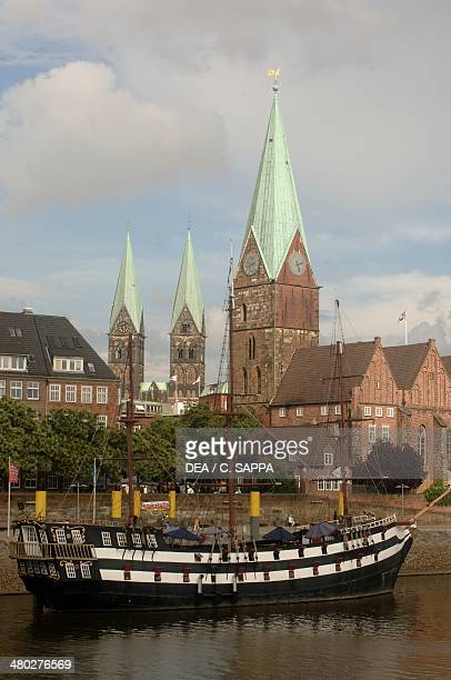 Sailing ship moored along the river Weser with the towers of Bremen Cathedral in the background on the left and Marktkirche Unser Lieben Frauen on...