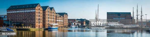 Sailing ships in boatyard overlooked by warehouses Gloucester docks panorama