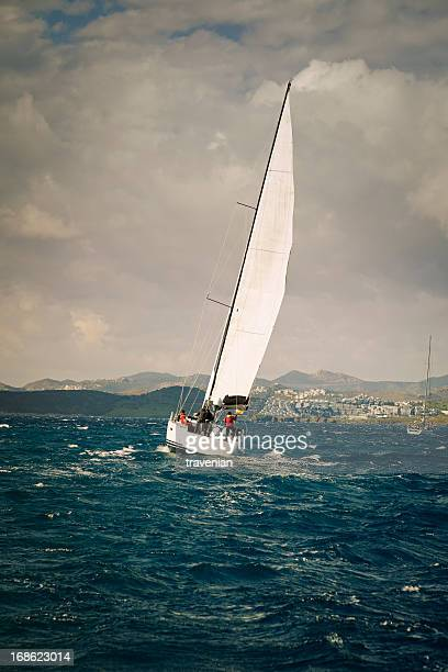 Sailing team on yacht and stormy weather
