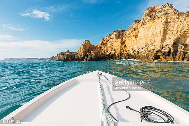 Sailing the boat among rock formations in Algarve, Portugal