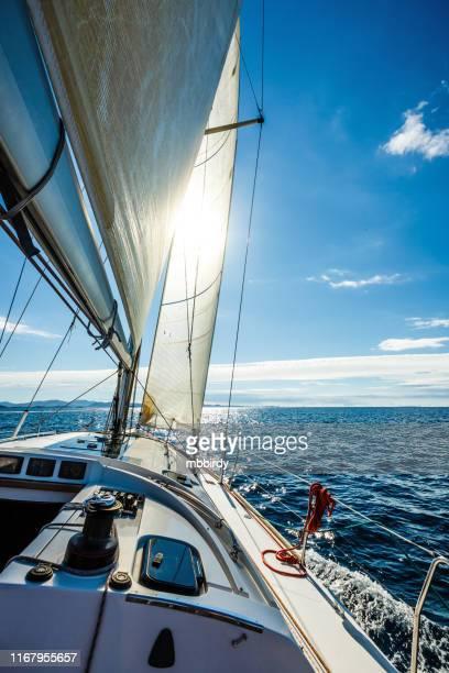 太陽に向かってヨットで航行 - セールボート ストックフォトと画像