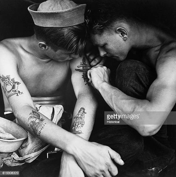 A sailor aboard the USS New Jersey inspects another sailor's tattoos December 1944 | Location aboard the USS New Jersey Pacific Ocean