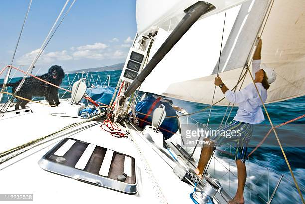 A sailor adjusts a sail with a dog on the bow during a race