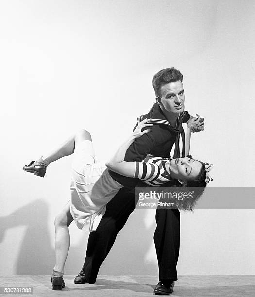 A sailor and a girl are shown jitterbugging He holds her down in a dipped position Ca 1940s