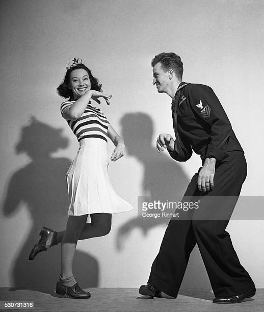 A sailor and a woman are shown jitterbugging Her hand is bent and he is slightly bent at the waist Ca 1940s