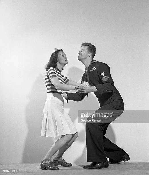 A sailor and a woman are shown jitterbugging They face each other and he sticks his chin out Ca 1940s