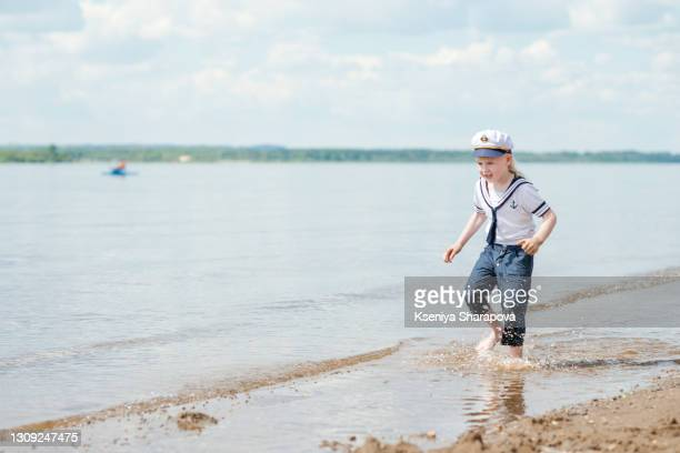 a sailor boy runs along the river's edge in summer-stock photo - sailor suit stock pictures, royalty-free photos & images