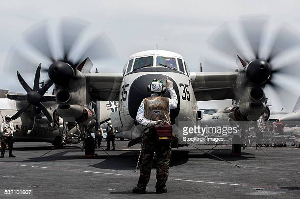 A Sailor directs a C-2A Greyhound on the flight deck of USS George Washington.