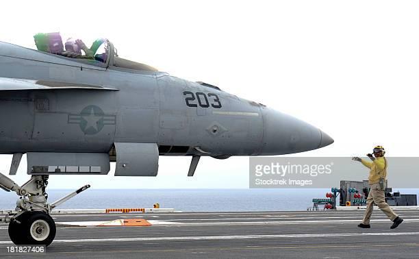 A  Sailor directs an F/A-18 18E Super Hornet across the flight deck of USS Nimitz.