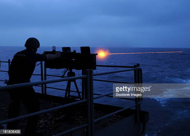 a sailor fires a .50-caliber machine gun on the fantail of uss george h.w. bush. - bang boat stock pictures, royalty-free photos & images