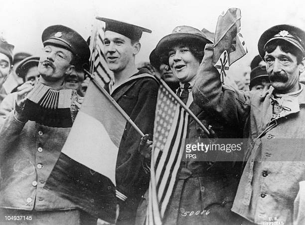 Sailor, French soldier and red cross worker celebrating on Armistice Day in Paris, France, November 11, 1918.