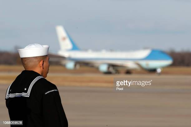 A sailor from the USS George HW Bush watches the US Air Force 747 being called 'Special Mission 41' land carrying the casket of the remains of former...