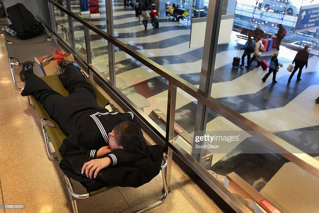 A sailor gets some rest on a cot in the hallway outside the USO as he waits to catch a flight at O'Hare International Airport on December 21, 2012 in Chicago, Illinois. Today is the busiest air travel day of the Christmas holiday, with an estimated 200,000 travelers expected to travel through O'Hare today.
