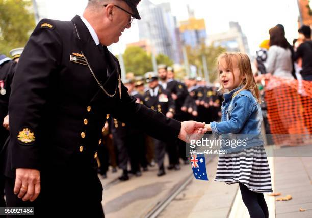 Sailor greets a young girl during the Anzac Day parade in Melbourne on April 25, 2018. - Tens of thousands of Australians and New Zealanders turned...