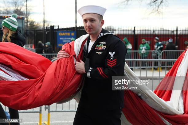 Sailor helps carry the flag during the Playoff game between the Seattle Seahawks and the Philadelphia Eagles on January 5 at Lincoln Financial Filed...