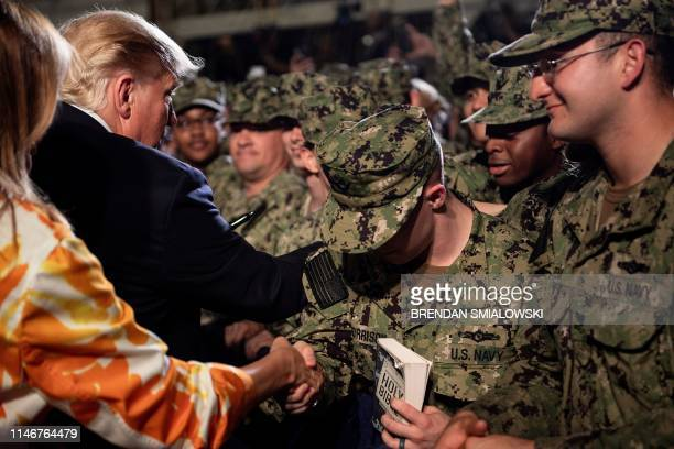 A sailor holds a bible while US President Donald Trump greets troops with US First Lady Melania Trump after speaking onboard the USS Wasp May 28 in...