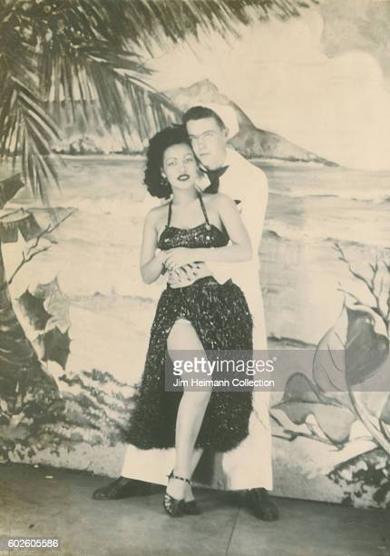 Sailor hugging woman in hula skirt Arcade photo depicting Diamandhead and beach