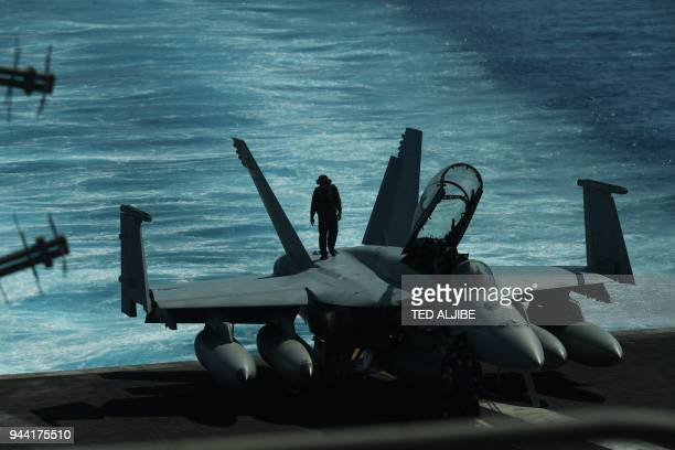TOPSHOT A sailor inspects atop an FA18 hornet fighter jet during a routine training aboard US aircraft carrier Theodore Roosevelt in the South China...