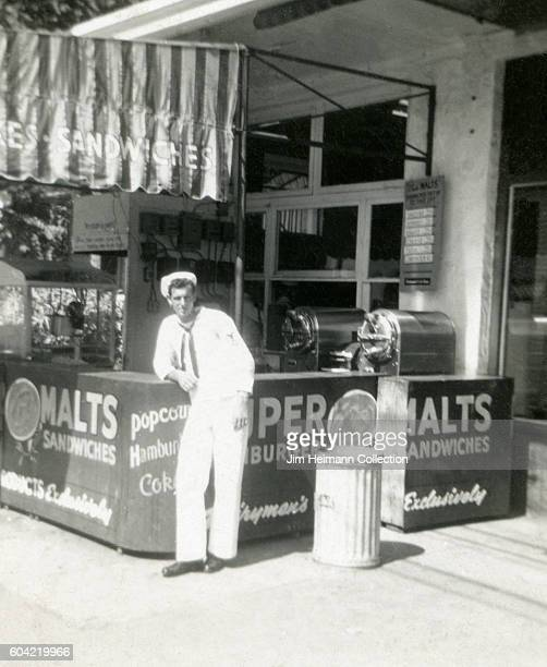 Sailor leaning on outdoor counter of refreshment stand advertising malts hamburgers sandwiches Coke and popcorn