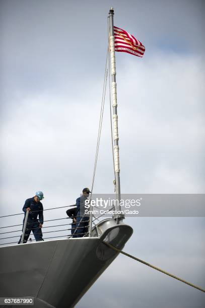 A Sailor lowers the Navy jack aboard the Arleigh Burkeclass guidedmissile destroyer USS Preble as it prepares to depart Naval Base San Diego for a...