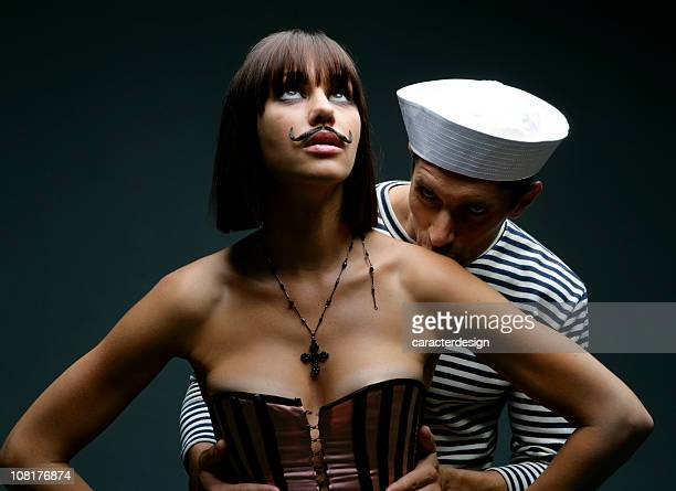 Sailor Man Kissing Young Woman Wearing Fake Mustache