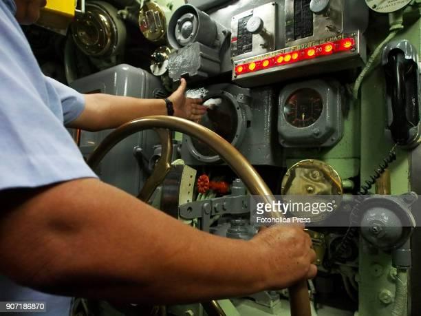 A sailor maneuvering depth rudders wheel in the control room of the BAP Abtao submarine of the Peruvian Navy The ship a Mackerel class submarine...