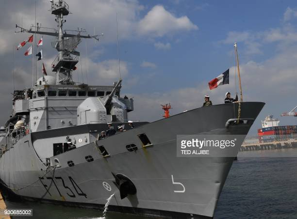 A sailor of French navy frigate Vendemiaire raises a national flag as it docks at the international port in Manila on March 12 2018 FNS Vendemiaire a...