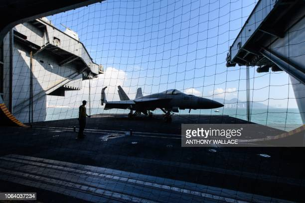 A sailor on board the US Navy's USS Ronald Reagan aircraft carrier stands on a lift transporting a singleseat F/A18E Super Hornet to the lower deck...