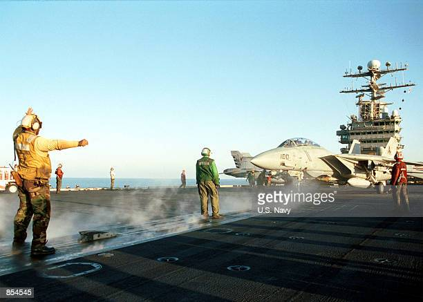 """Sailor prepares an F-14D """"Tomcat"""" for launch December 6, 2001 aboard the USS Carl Vinson. The USS Carl Vinson is conducting missions in support of..."""
