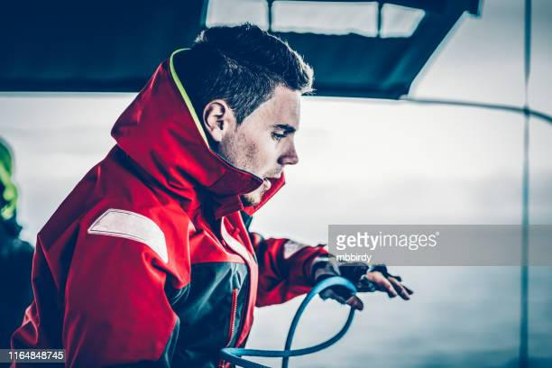 sailor preparing to wind rope on winch with hands - sailing stock pictures, royalty-free photos & images