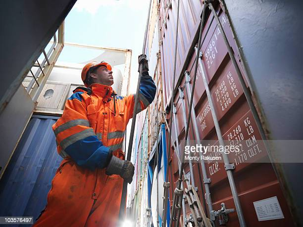 sailor pulling a rope in cargo bay - dock worker stock photos and pictures